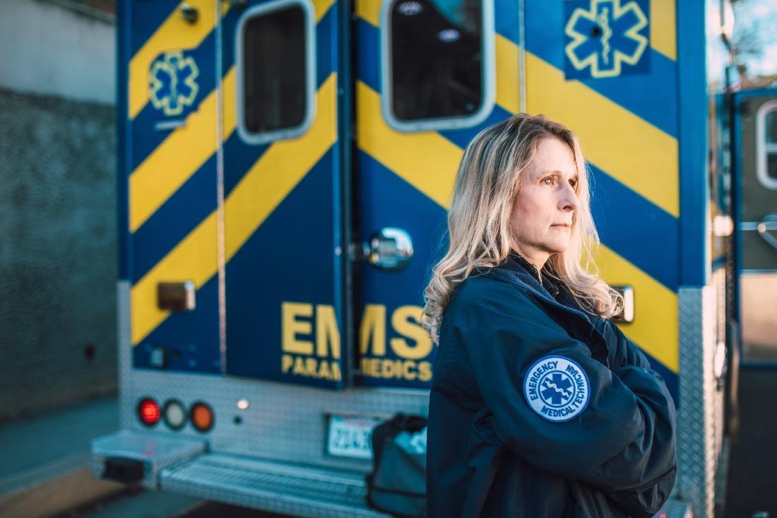 Somber EMT stands in front of an EMT ambulance vehicle.