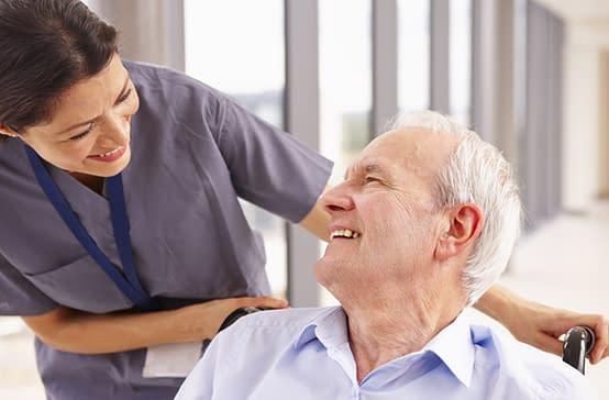Elderly patient in wheelchair smiling at nurse
