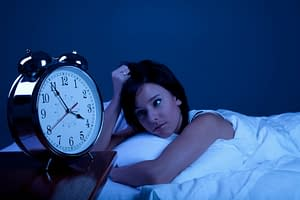 Girl in bed not able to sleep with a clock in the foreground
