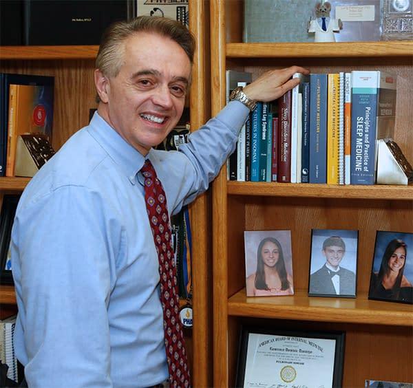 Sleep specialist posing beside bookshelf
