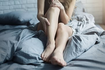 female with tired legs in bed