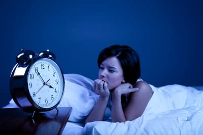 woman in bed with insomnia staring at alarm clock