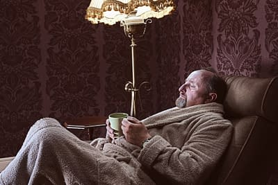 older man in robe with mug in a recliner
