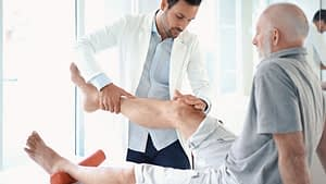 elderly man sitting on exam table with male doctor examining his knee