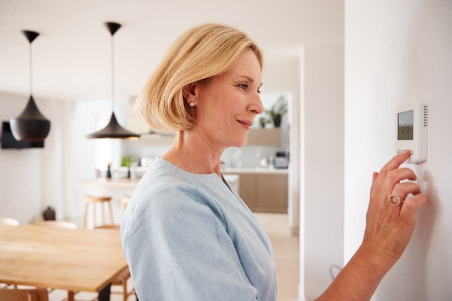 Woman adjusting thermostat in modern home