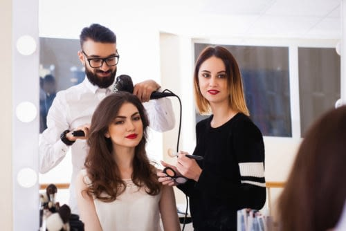 a male and female cosmetologists styling hair