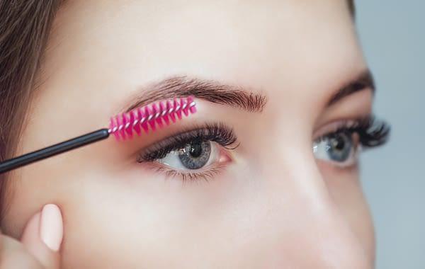 Woman brushing her eyelash extensions