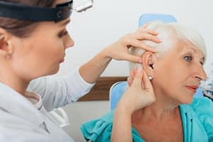 doctor fitting a hearing aid for patient