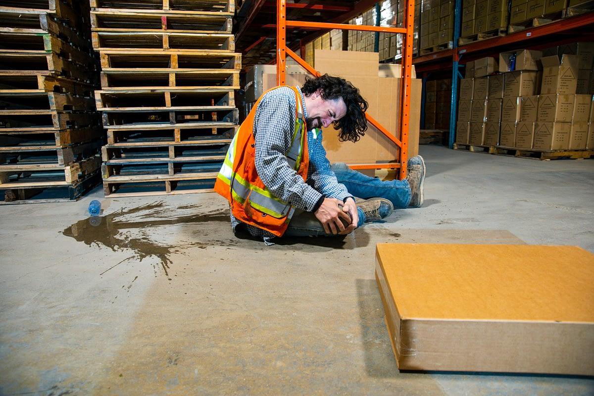 injured man sitting on warehouse floor holding his knee