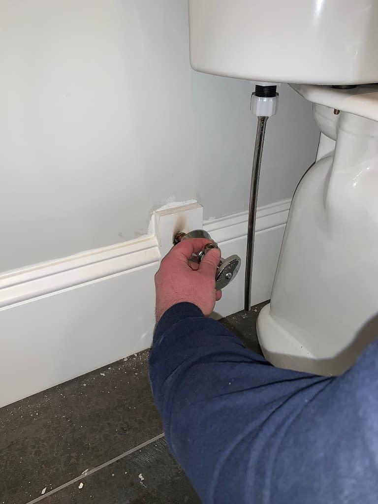 Man inspecting hardware behind toilet