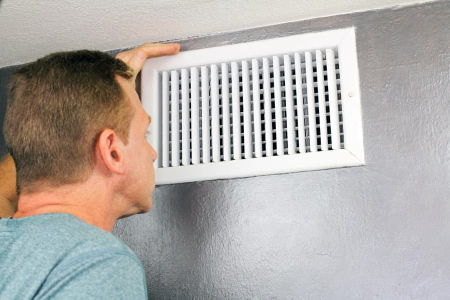 Man Inspecting Home Air Vent for Allergens