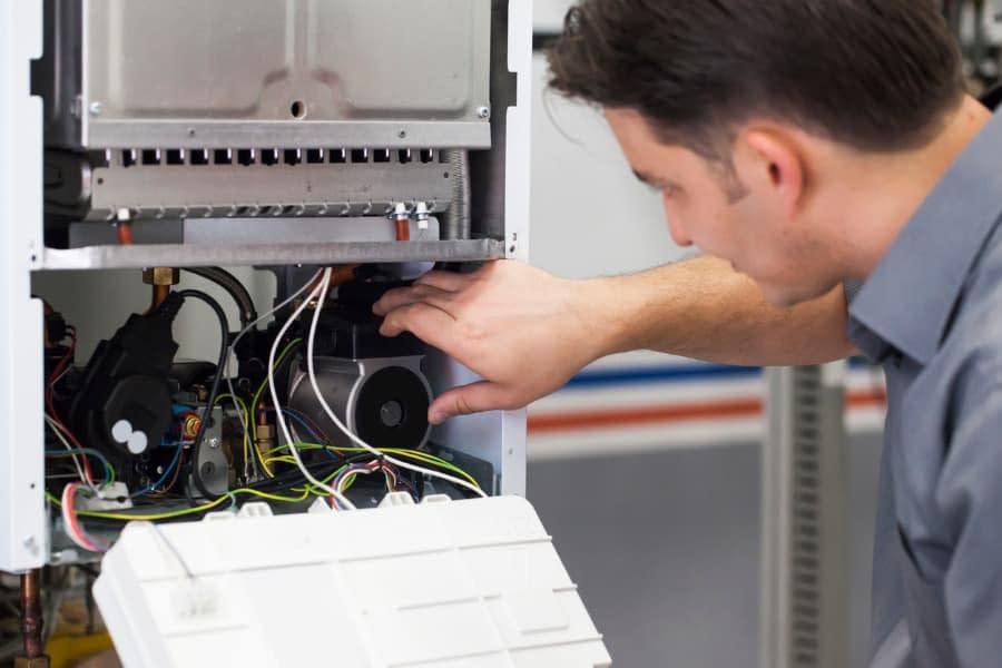 male technician repairing a heater boiler