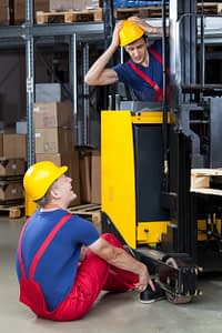 construction worker sitting on ground trying to release his foot from under a forklift