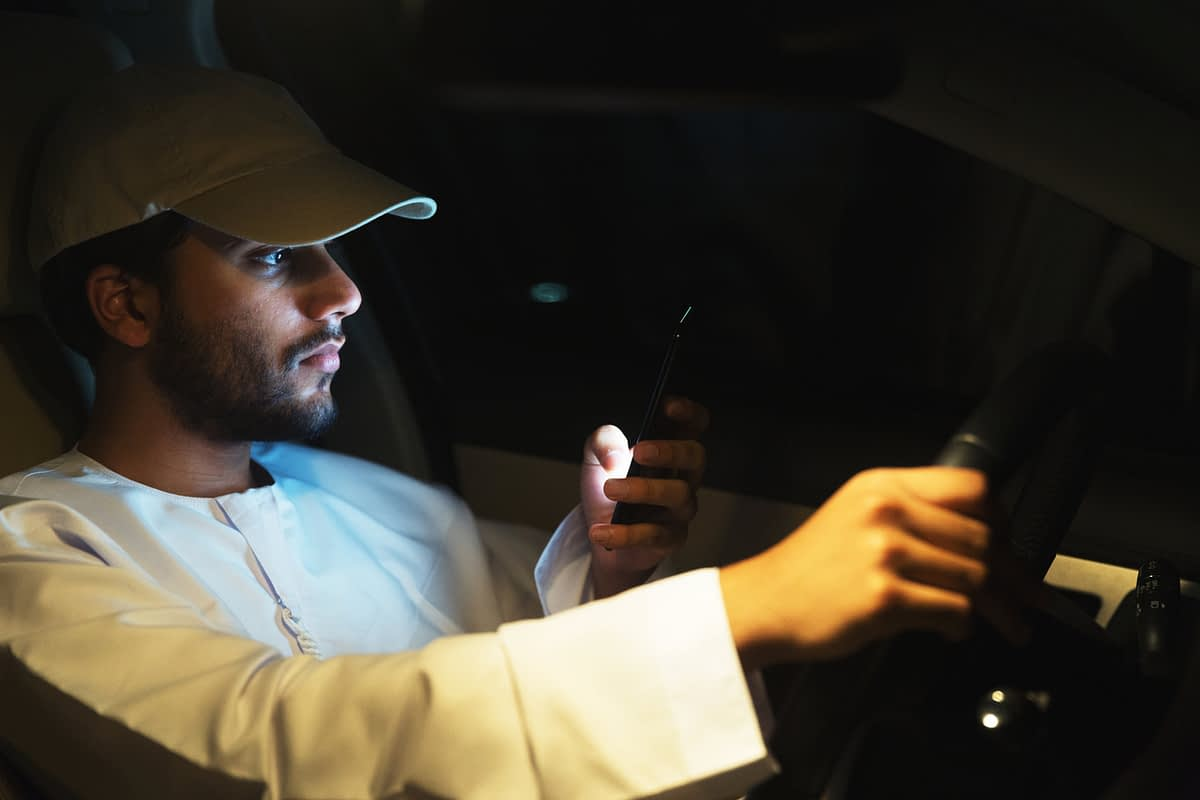 Distracted young man texting while driving
