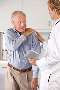 Doctor Examining Shoulder Pain in Elderly Man