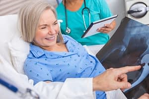 Elderly Patient Being Shown Hip X-Ray by Surgeon