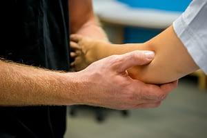 Doctor Examines Patient's Elbow