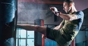 Man Kickboxing Punching Bag