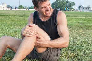 man sitting on ground holding his left thigh and knee