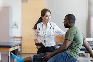 Patient discusses ankle injury with doctor
