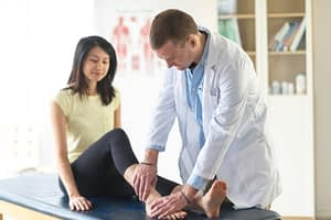 Doctor checks patient's sprained ankle