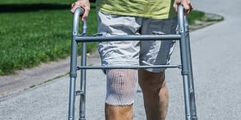 person walking outside with a walker and a bandaged right knee