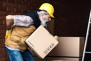 worker lifting a box and holding his back with a pained expression