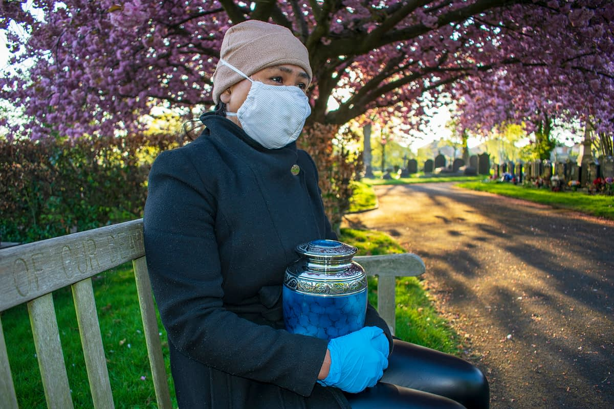 woman wearing a mask sitting on a park bench in a cemetery holding an urn