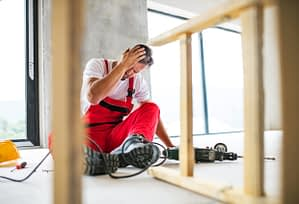 male construction worker sitting on floor holding his head after falling off ladder