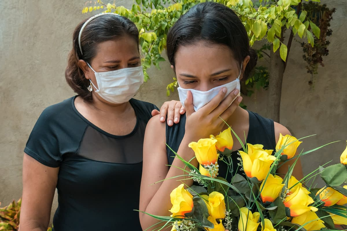 two women wearing black and masks holding flowers at a cemetery