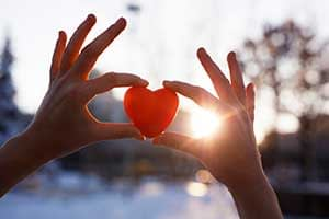 Hands holding heart cutout.