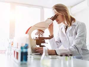 Researcher examines sample.