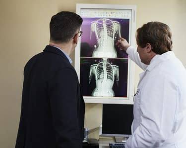 doctor pointing x-ray result beside man wearing black suit