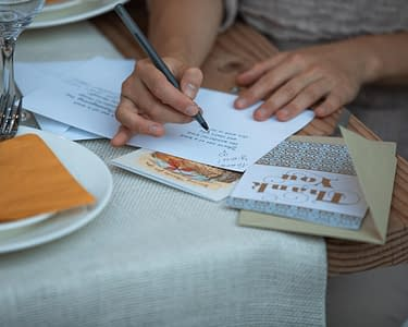 writing thank you note at thanksgiving dinner table