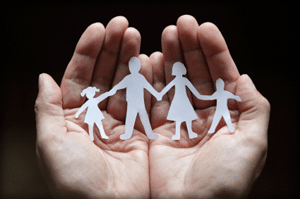 Cupped hands holding paper cutout of family