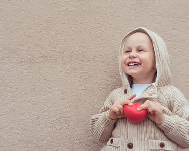 Joyful young boy holds red heart.