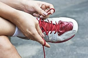 person tying red shoelaces