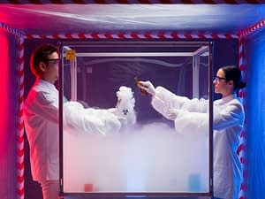 : a man and a woman mixing chemicals in a steamy sterile chamber labeled as biohazardous