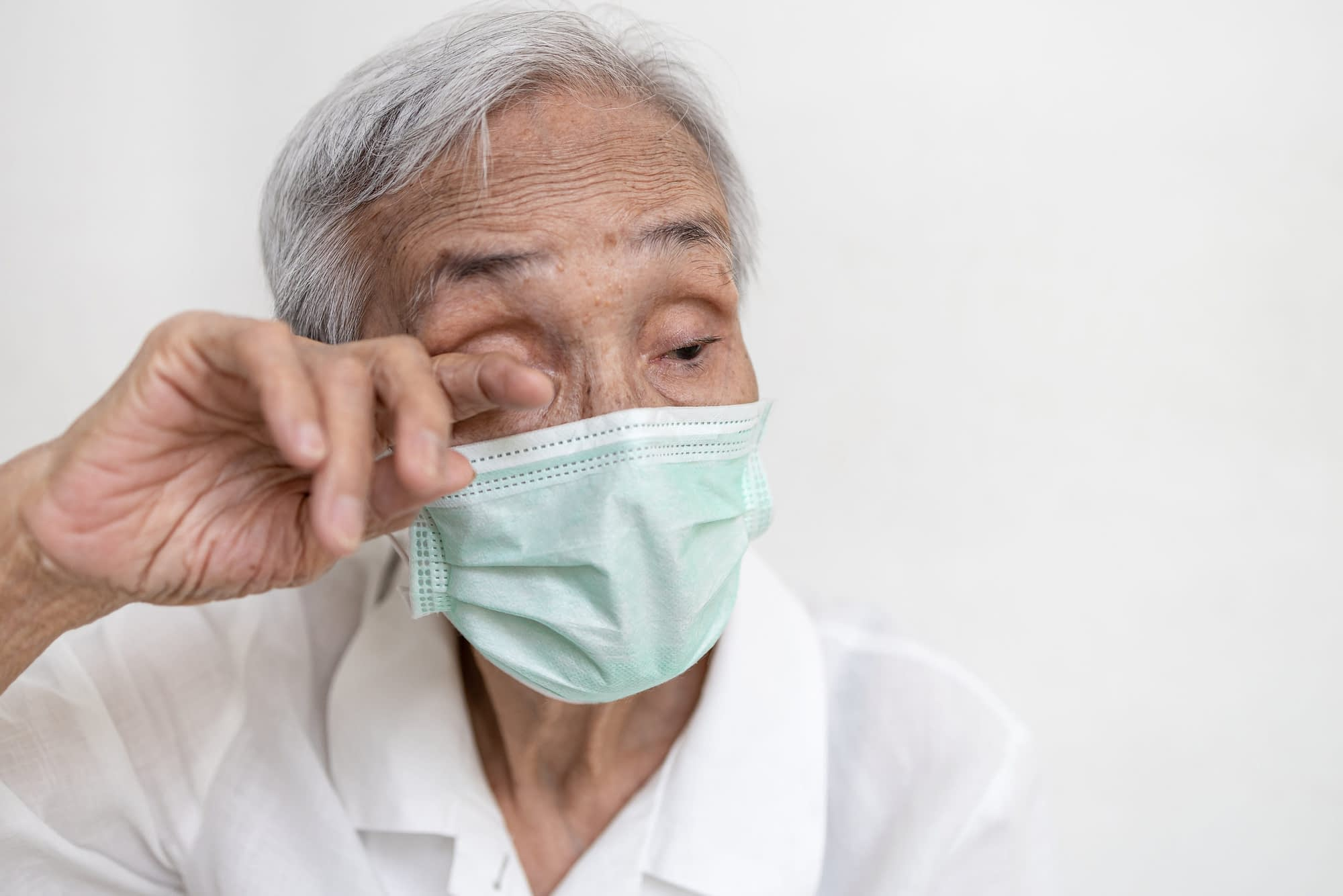 Asian senior woman in medical protective mask rubbing her eyes,Do not touch eyes with her dirty hand,avoid touching to protect form COVID-19,risk of Coronavirus infection,Don't touch face,health care