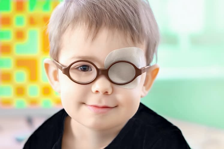 A little boy wearing glasses and an eye patch (plaster, occluder) undergoes a hardware vision treatment to prevent amblyopia and strabismus (squint, lazy eye). Child congenital vision disease problem.