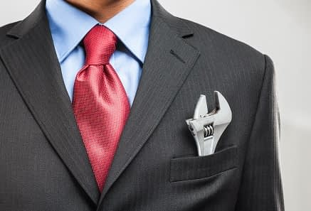 Man in suit with wrench in breast pocket