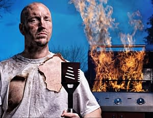 man with burnt shirt standing in front of a grill that's on fire
