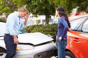 a man and woman arguing after a car accident