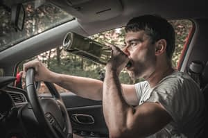 man in the driver's seat of a car drinking out of a wine bottle