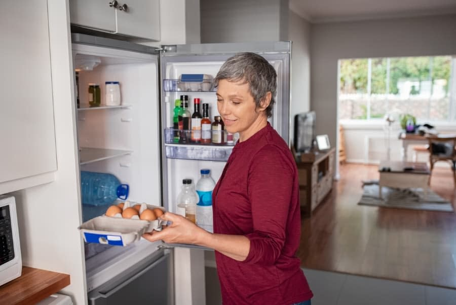 Woman Taking Eggs From Refrigerator
