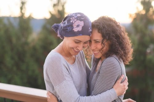 A beautiful young woman fighting cancer and wearing a head wrap embraces her sister. They are tightly holding each other and she is looking down and smiling. Her sister is also smiling. They are standing outdoors and there are mountains and trees in the background.