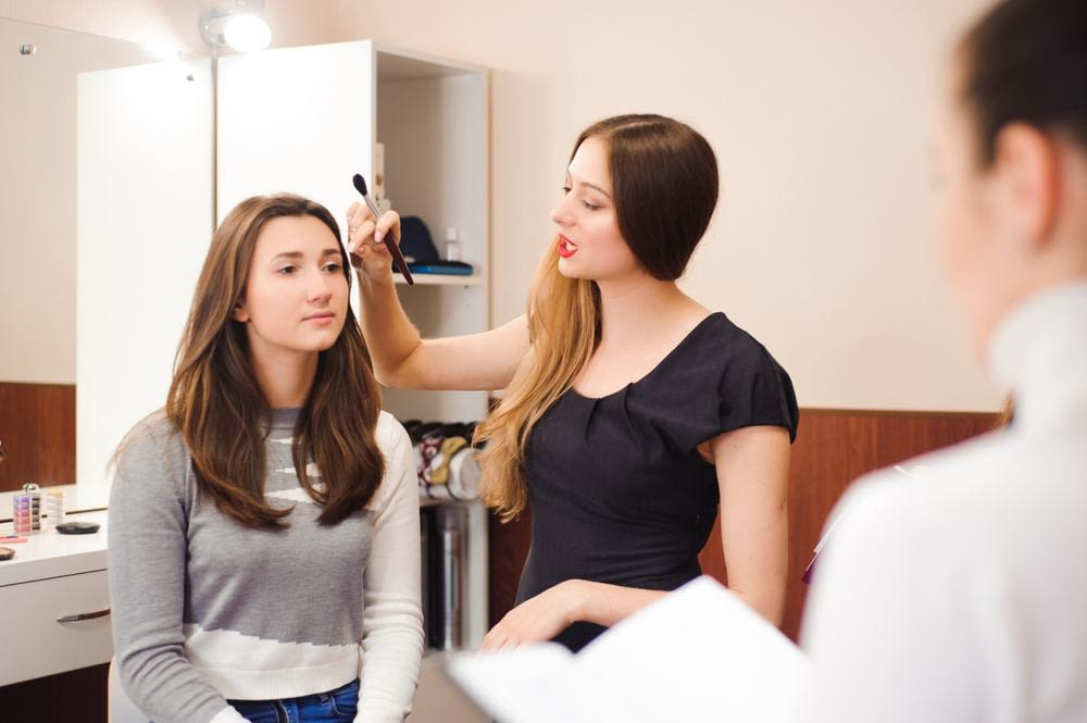 a beauty instructor demonstrates makeup application in a classroom
