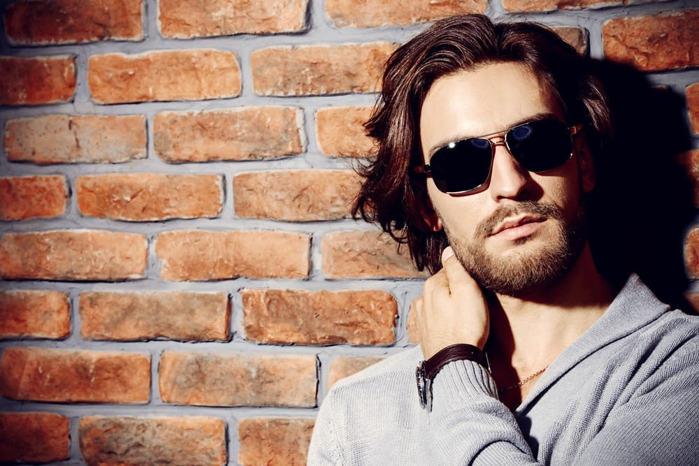 stylish man with long hair and beard wearing sunglasses in front of a brick wall