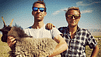 Two hot guys in sunglasses holding a goat.
