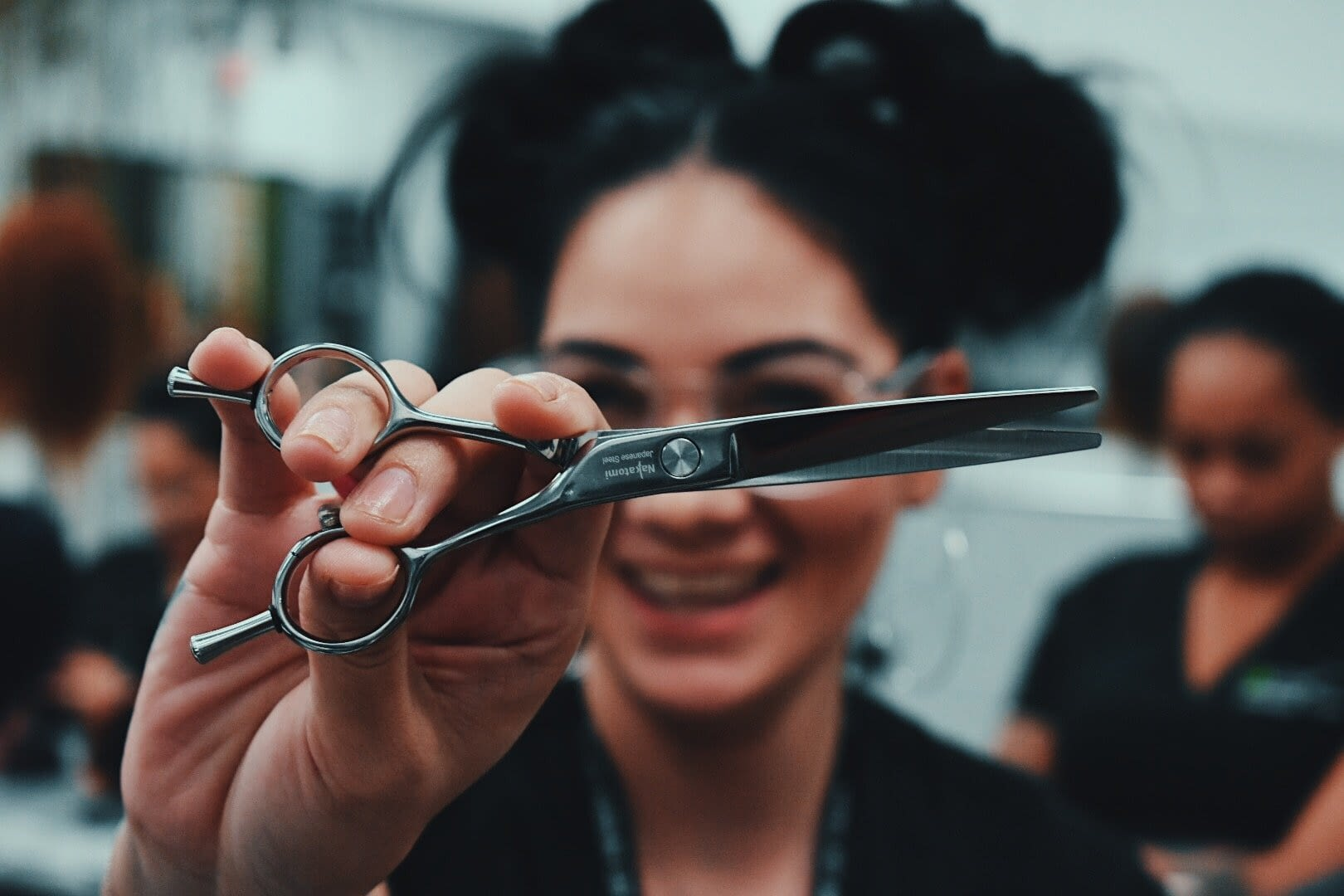 cosmetologist holding out pair of scissors